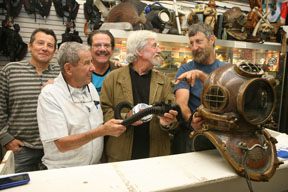 Dive N' Surf dive master Jocko Robinson (right) shows off a vintage double hose regulator and a hard hat to Jean-Michel Cousteau. Joining the group are Billy, Bob and Robbie Meistrell. Photo by Kevin Cody