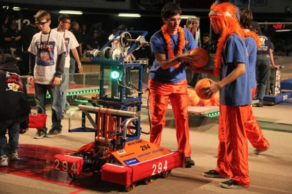 Chris Golden and Michael McPherson situate the team's robot on the competition court. Photo by Alene Tchekmedyian