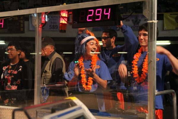 Chris Golden and Michael McPherson clap and cheer after they controlled the team's robot to balance on the teeterboard. Photo by Alene Tchekmedyian