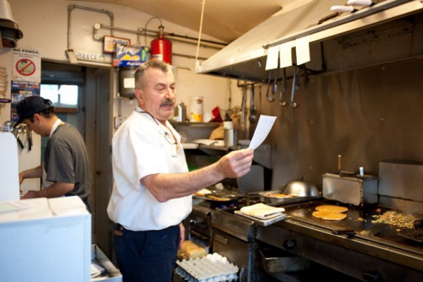 George Anagostu, the owner of the Cozy Cafe, checks a breakfast order. Photo by Chelsea Sektnan.