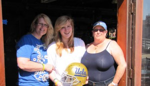 Friends and neighbors came together for a silent auction at On the Rocks on Saturday for Nick Ekbatani, who lost his left leg in a motorcycle accident earlier in the summer. His mother Tracy, his sister Kaylah and Cindy Pearson hold up a Jim Mora signed UCLA helmet, donated for the silent auction. They raised around $1,000. To donate, visit www.gofundme.com/venb8