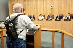 Dan Buck stands before the city council to discuss the health impacts of the power plant. Photo by Chelsea Sektnan