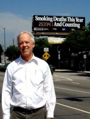 Candidate Bill Bloomfield in front of the anti-smoking sign he and his father erected in Westwood 25 years ago. Photo courtesy of the Bloomfield campaign.