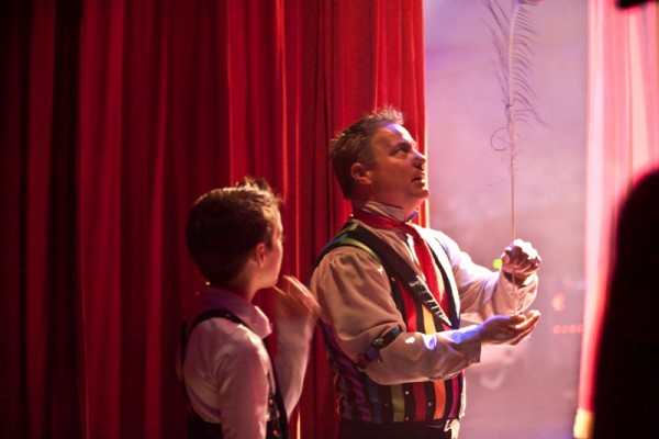 Jon Weisse teaches his son Max how to balance a peacock feather shortly before going on stage. The children who travel with the show go to school every day except Sunday and are only allowed to participate in certain acts.