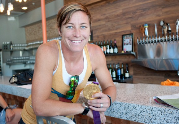 "U.S. soccer star Abby Wambach shows off her gold medal at Hot's Kitchen in Hermosa Beach after returning from the London Olympic Games. ""It gets me a lot of free stuff,"" she said. Photo by Chelsea Sektnan"