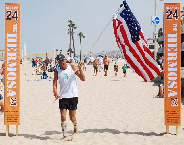 Manhattan Beach native Patrick Sweeney crosses the finish line at the Hermosa 24 Ultramarathon, breaking his own Guinness World Record for Distance Running in the Sand for 24 Hours. Photo by Randy Angel