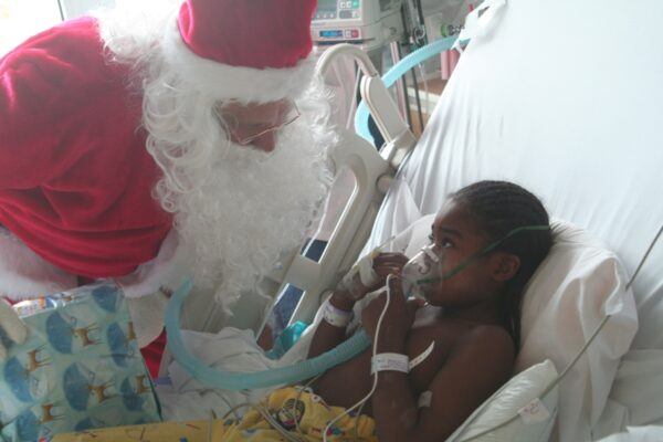 Santa, brought to Harbor-UCLA hospital by Cheer for Children, provides holiday cheer and presents for a little girl. Photo by Mark McDermott