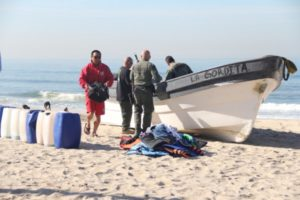 Los Angeles County lifeguards and sheriffs unload fuel, clothes and shoes from a panga that was beached on the Manhattan Beach/El Segundo border March 21. Photo by Alene Tchekmedyian