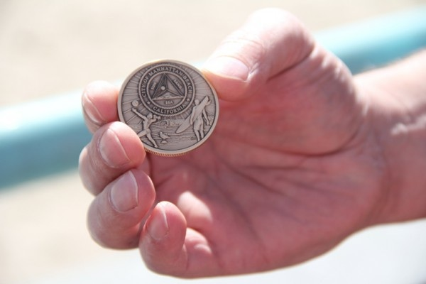 A special Manhattan Beach centennial coin designed by longtime resident and coin enthusiast James Gill. Photo by Alene Tchekmedyian
