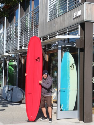 "Nikau Kai recently launched their own shop brand of Surfboards. Here shop manager and group member of the band ""Bullys and Matadors"" holds the latest noserider. It's best described as a simple 9'6"" noserider with a traditional feel, yet highly explosive."