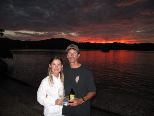 Jackie and Jake Adams pose with Hokule'a moored in the background in Fiji.