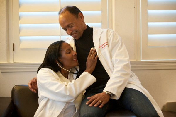 Dr. Karol Watson listens to a heart whose beat she knows well – that of her husband, Dr. Christopher Branche. Photo by Chelsea Sektnan