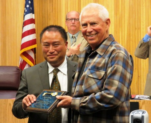 Former treasurer Ernie O'Dell receives a key to the city from Mayor Mike Gin after announcing his early retirement, ending a nearly 18-year career as the city's treasurer. Now, three candidates are running to fill his place. Photo by Rachel Reeves