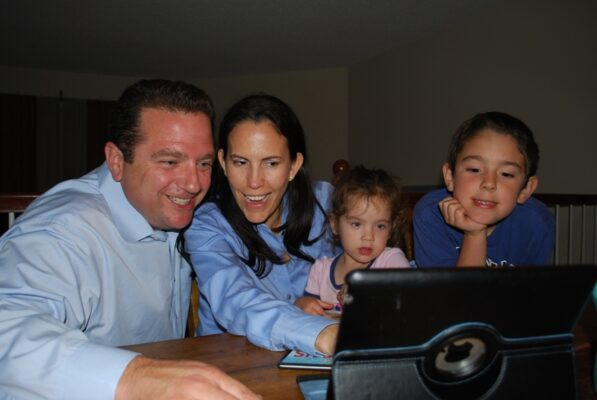 District 4 leading candidate Stephen Sammarco checks election results on the web with wife Ofelia and their two young children. Photo courtesy of Stephen Sammarco