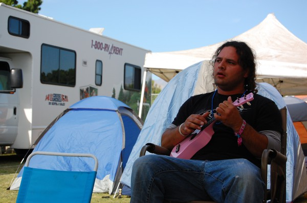 Alex, a Mexican-Hawaiian from Redondo Beach, plays a few tunes at the campsite before reporting to his shift.
