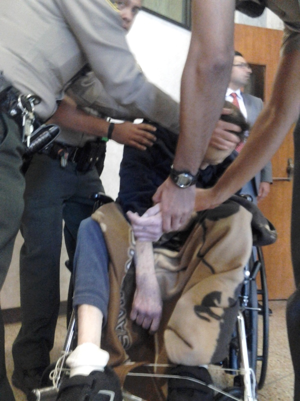 Los Angeles County Sheriff's Deputies prepare to move Larry Delassus from his wheelchair to the floor where they performed CPR on him until paramedics arrived at the Torrance Courthouse on Dec. 19. Photo by Ed Pilolla