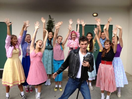 Belasco Theatre Company presents the musical Bye Bye Birdie, June 21-July 7 at the Hermosa Beach Playhouse, 710 Pier Avenue, Hermosa Beach.  Pictured are Conrad Birdie (Kyle Cook) surrounded by his adoring fans, Rachel Peter, Ava Alexiades, Gillian Cullen, Kylie Grogan, Alex Foss, Isabella Polizzotto, Sabrina Harris, Brianna Powell and Emily Schugel. Tickets are $17 or $15 for children under 12 and seniors. Groups of 10 or more, $15 each. For more information please call (310) 379-4208 or visit www.belasco.org. So buy, buy tickets to Belasco Theatre's Bye Bye Birdie. Photo by Shanti Belasco-Glynn