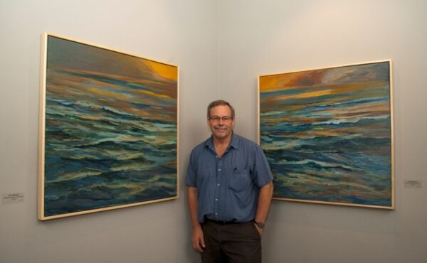 Artist and print shop/gallery owner Ron Libbrecht with two of his recent paintings. Photo by Gloria Plascencia