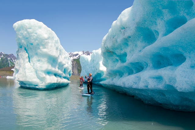 Liquid Adventure's Chris Mautino and Pam Sousa paddling through ice alley in Bear Glacier.