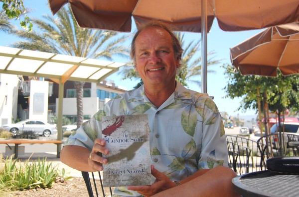 Darryl Nyznyk, a 34-year Manhattan Beach resident, with his third published novel, The Condor Song. Photo by Esther Kang