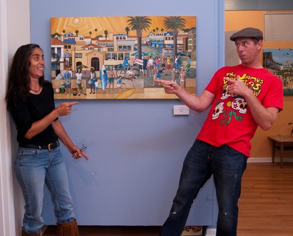 """Bob Mackie's painting, """"Life's a Beach,"""" features Sabina Sandoval and Cameron Clarke, both of whom are posing next to it. Mackie's solo show opened last Saturday at 608 North in Redondo Beach. Mackie's work is up through Oct. 13. Photo by Gloria Plascencia. (310) 376-5777 or go to 608north.com."""