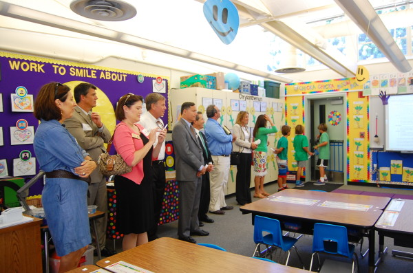 The tour group visits Mrs. Mushet's first grade classroom, where non-toxic cleaning supplies and brown compostable paper towels are discussed.