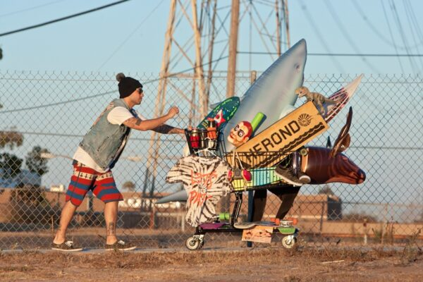 Mirko Antich and a cart brimming with some of the things that inspire his art -- grunge, beach culture, skateboarding, the ocean, and punk music. Photo by Chris van Berkom