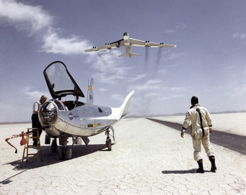 NASA pilot Bill Dana watches a Boeing NB-52B carrier aircraft fly overhead after a successful test flight of the Northrop HL-10 lifting body at NASA Dryden Flight Research Center, Calif., 1969. NASA photo. © The Huntington Library, Art Collections, and Botanical Gardens