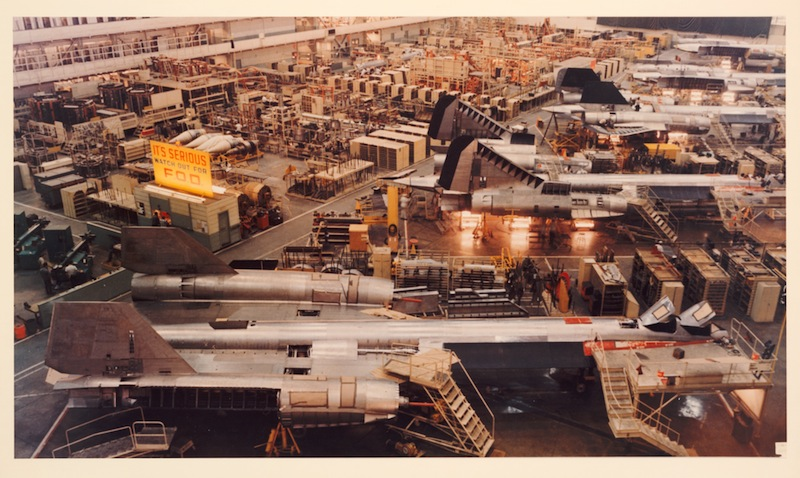 """SR-71 Blackbirds on the production line at Lockheed Skunk Works, in the mid-1960s. A sign on the wall warns """"Watch out for F.O.D."""" A loose bolt or rivet that could be sucked into a jet engine was potential """"foreign object damage,"""" costing millions of dollars to repair. © The Huntington Library, Art Collections, and Botanical Gardens"""