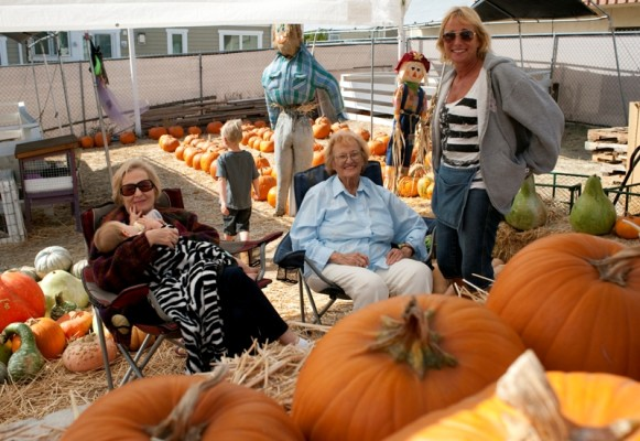 Family member Pam Barker holds 8-month-old granddaughter Sophia DeLuca while 4-year-old Michael DeLuca explores the pumpkin patch in Hermosa Beach. Ann DiMeglio, one of the first family members to own a pumpkin patch sits next to the current owner, Debbie Perry. Photo by Chelsea Sektnan