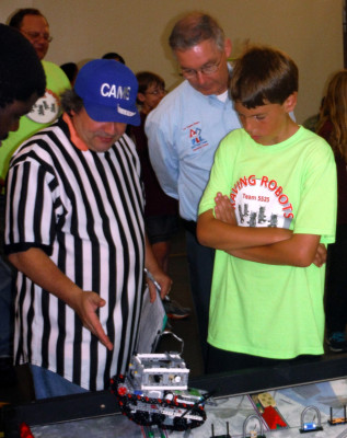Raving Robots' Sean McQuiggan listens to referee's scoring decision overseen by LeRoy E. Nelson, Operational Partner of the Los Angeles Region FIRST LEGO League