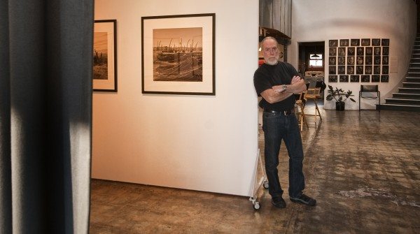 "Ray Carofano in his gallery, with images from ""The Land of Broken Dreams"" to the left and ""Faces of Pedro"" on the far wall behind him. Photo by Gloria Plascencia"