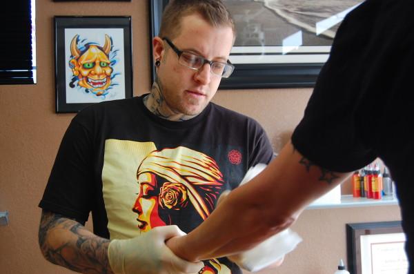 Jeffrey Barnett, 28, prepares a client's arm for a new ink job.