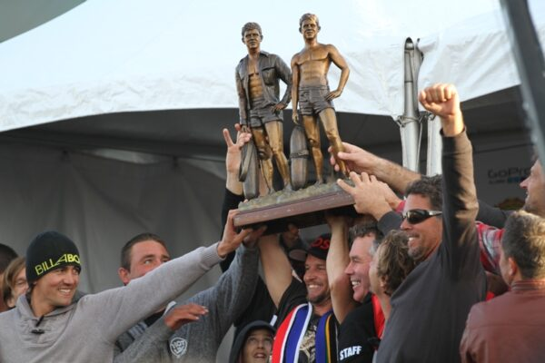 """Grant """"Twiggy"""" Baker hoists the Body Glove Mavericks Invitational Trophy trophy with help from fellow finalists Greg Long and Anthony Tashnick, contest director Jeff Clark and 2013 winner Peter Mel. The trophy depicts Body Glove co-founders Bill and Bob Meistrell. It was sculpted by Hermosa Beach surfer Chris Barella. Photo by Mike Balzer"""