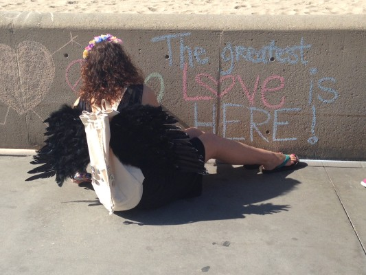 Cyndi Holt draws a Funism heart on the Strand on Friday during the peaceful protest. Photo by Chelsea Schreiber