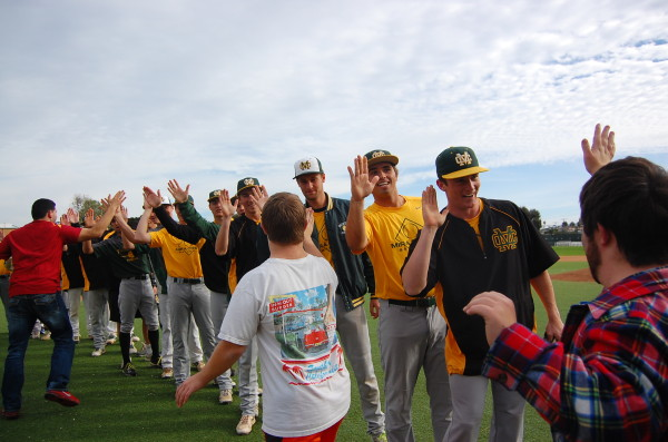 Josh Ramos, Steven King and Michael Geresi -- special needs students at Mira Costa High School -- exchange high fives with the Mustang varsity baseball team at the conclusion of the third annual Friendship Circle game Friday at Mira Costa's Osterhaus Field. Photo by Esther Kang