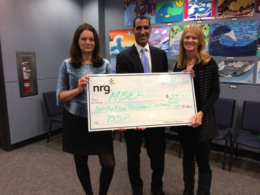 MBEF's Marija Kosanovich and Margo Thole accepts a $25,000 check from NRG Energy's Ahmed Haque at the Feb. 11 board meeting. Photo courtesy of Margo Thole
