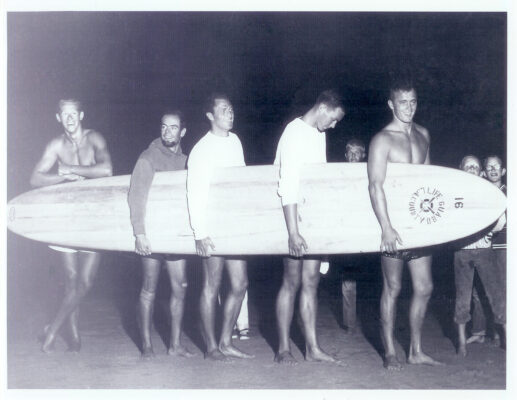 1956 International Surf Festival Taplin Bell champions Mike Bright, Bob Hogan, John McFarlane, Chip Post and Greg Noll, with a Velzy paddleboard.