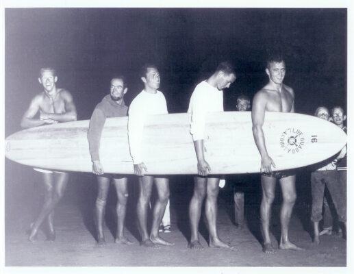 1956 International Surf Festival Taplin Bell champions Mike Bright, Bob Hogan, John McFarlane, Chip Post and Greg Noll, with a Velzy paddleboard.