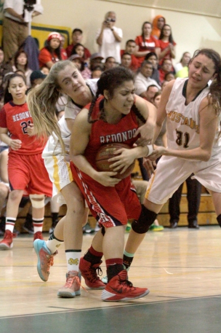 Redondo's Micaela Enriquez is wrapped up by Mira Costa's Alexa Underwood and Allie Navarette. Photo by Ray Vidal