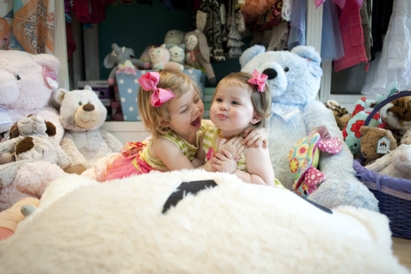 Piper and Ivy Freeman wear matching Giggle Moon outfits and play with stuffed animals at Bella Beach kids. Photo by Chelsea Schreiber