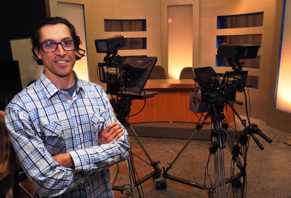 Michael Hernandez, Broadcast Journalism teacher at Mira Costa High, stands in front of the studio set his students use to tape the school's news broadcasts. Photo: Bruce Hazelton
