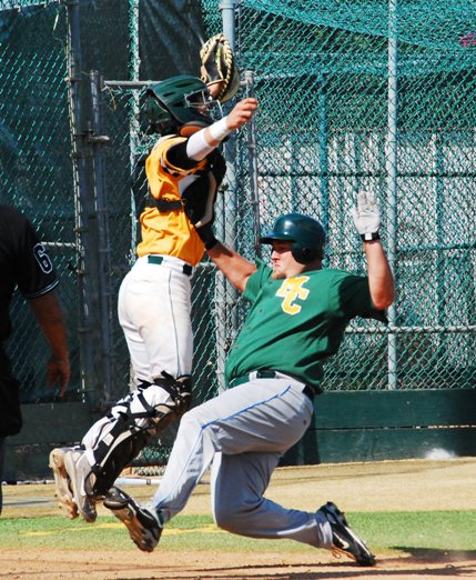 Sean Finnerty scores for the Alumni as the throw sails over the head of varsity catcher Brett Davis. Photo by Randy Angel