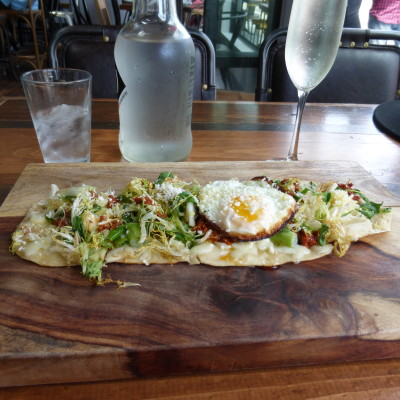The daily flatbread pizza special tends to experiment Pictured is a thin-crust pizza topped with three cheeses, Mexican chorizo, arugula, and a fried egg. Photo by Richard Foss