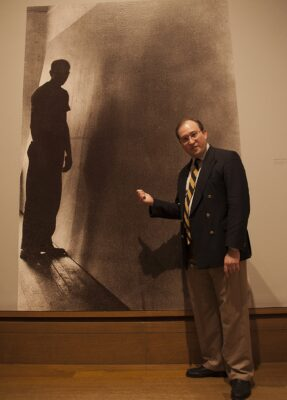 """Sean O'Harrow, director of the University of Iowa Museum of Art, at a preview showing of """"Mural."""" Behind him is a photograph by Bernard Schardt of Jackson Pollock with the unpainted canvas for his mural, 1943 (Pollock-Krasner House and Study Center, East Hampton, New York. Gift of Jeffrey Potter). Photo by Gloria Plascencia"""