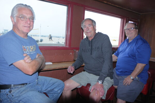 Semi retired construction worker Ed Barden, retired engineer Walt Armstrong and retired attorney Matt Schumacher have been meeting almost daily at the Poop Deck since the mid 1970s, when they played volleyball outfront. Photo by Kevin Cody