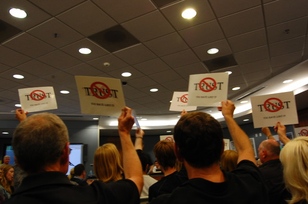Attendees hold up their signs in protest as administrators explain the accounting oversight. Photo by Esther Kang