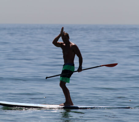Dave Schaefer of Don't Just Surf gives the SCUBA signal for a shark sighting at 44th Street in Manhattan Beach on Thursday.