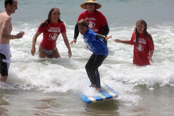 Hermosa Beach Chevron Surf Camp instructor Emma Huschel and director Vince Ray share the stoke with a young camper. Photo courtesy of Vince Ray