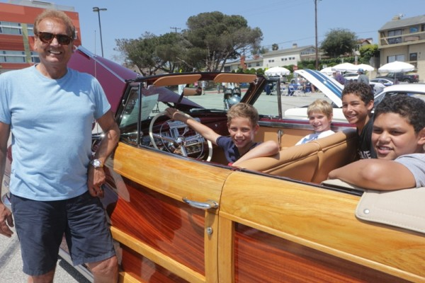 John Altamura and William Liner, Zach Wohl and Andrew and Matthew Liner of Kids for Laos Orphans. They are sitting in Altamura's 1947 Chrysler Town and Country Convertible Woody.